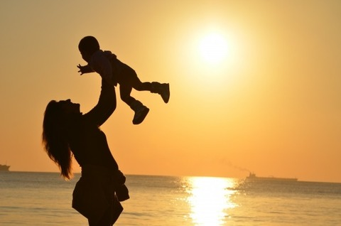 silhouette-of-mother-holding-her-baby-aloft-at-seaside